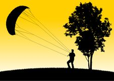 Man Flying Stunt Kite on Hill by a Tree Royalty Free Stock Photography