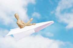 Man flying in a toy paper plane Stock Photo