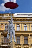 Man flying with umbrella statue in Prague Europe. Businessman flying with red umbrella statue hanging in Prague, Europe in front of an old architectural building Royalty Free Stock Photos