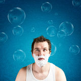 Man with foam on the face. Looking at bubbles Stock Photography