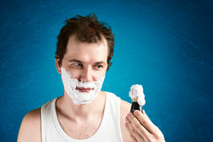 Man with foam on the face. Looking on little brush Stock Photography
