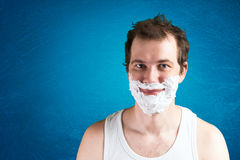 Man with foam on the face. Smiling Stock Image