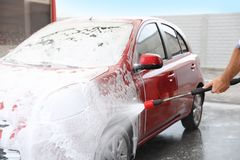 Man foaming red auto at car wash stock photos
