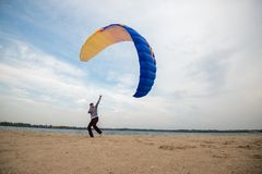 Man, with focused face, control a kite, paraglider. While training on the beach in the city park. Wide angle stock photography