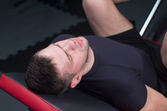 Man focused on training legs on the machine in the gym Royalty Free Stock Photography