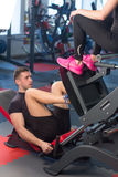 Man focused on training legs on the machine in the gym with trainer Stock Photos