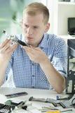 Man focusing during computer fixing Royalty Free Stock Photos