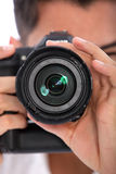 Man focusing his camera. With the lens pointed directly at the viewer, close up view Royalty Free Stock Photo
