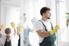 Man focusing on work. Man in protective clothing and yellow gloves focusing on cleaning work stock images