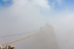 Man in fog over chasm. Man crossing the chasm on the hanging bridge in fog (focus on the middle of bridge Royalty Free Stock Photo