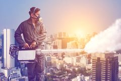 Man fogging to eliminate mosquito for preventing spread dengue fever and zika virus. In the city background royalty free stock image