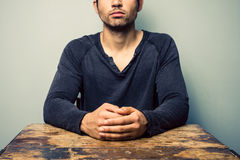 Man with folded hands sitting at desk Stock Photos
