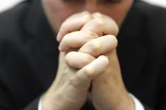 Man folded his hands together with blurred face. And praying stock photos