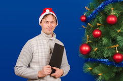 The man with the folder costs near an elegant New Year tree and Stock Image