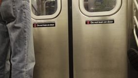 A man with a folder riding a train subway in New York. A man with a yellow folder riding a subway train in New York, the train doors open and the man is leaving stock footage