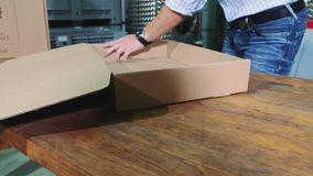 Man folding cardboard box. Around fragile item in garage stock footage