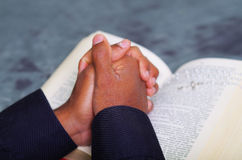 Man folding hands praying with open bible lying in front, seen from behind models head, religion concept Royalty Free Stock Image