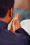 Man folding hands praying with open bible lying in front, seen from behind models head, religion concept Stock Photography