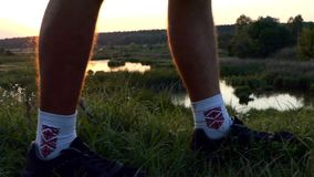 Man in folk socks walking on the grass at sunset. stock video footage