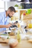 Man following recipe on digital tablet and cooking tasty and healthy food in kitchen at home royalty free stock photos