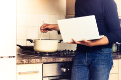 Man following recipe on his laptop computer. Young man is standing by his cooker and stirring a pot while reading on his laptop, possibly following a recipe Stock Photo
