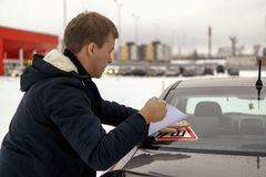 Man pastes thorn sign sticker on car window. Man following the rules and pastes a thorn sign sticker on car window, as Traffic Laws require Royalty Free Stock Photo