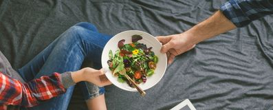Man food bed beloved woman. Concept love and care. Man brought a salad in bed to his beloved woman. Concept of love and care Royalty Free Stock Photos