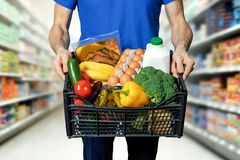Man with food box in hands at grocery store. Aisle royalty free stock photography