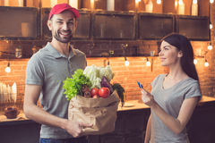 Man with food from food delivery service. Food delivery service. Young men smiling and looking at camera while bringing fresh food. Young women paying with Stock Photo