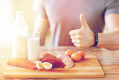 Man with food rich in protein showing thumbs up. Sport, fitness, healthy lifestyle, diet and people concept - close up of man with food rich in protein showing royalty free stock image