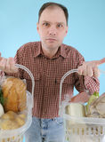 Man with foods in supermarket baskets Royalty Free Stock Image