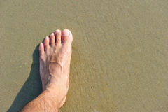 Man foot on beach Stock Photo