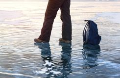 Man foot at ice surface lake Baikal. Winter sport travel. Man foot at ice surface at lake Baikal. Winter activity and travel concept Stock Photo