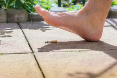 Man foot steps on a hot cigarette barefoot in the summer stock photo