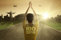 Man with football clothes and raise hands at road Royalty Free Stock Images