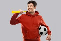 Man or football fan with soccer ball and vuvuzela. Sport, leisure games and people - happy man or football fan in red hoodie with soccer ball and vuvuzela over stock images