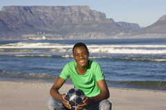 Man With Football On Table Mountain Beach. Portrait of a smiling African American man with football on Table Mountain beach Stock Photos