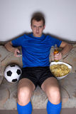 Man in football uniform sitting in living room Royalty Free Stock Images