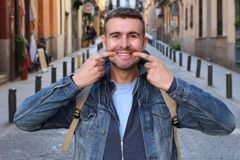 Man forced to smile outdoors.  royalty free stock photo