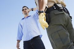 Man Forced To Take A Field Sobriety Test. Middle aged men forced to take a field sobriety test by a police officer Royalty Free Stock Image