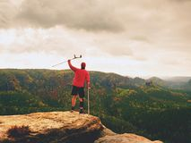 Man with forearm crutch. Hiker achieved mountain peak with broken leg in immobilize Stock Image
