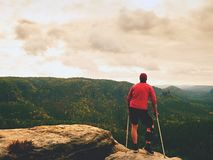 Man with forearm crutch. Hiker achieved mountain peak with broken leg in immobilize Stock Photos