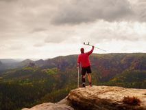 Man with forearm crutch. Hiker achieved mountain peak with broken leg in immobilize Royalty Free Stock Photography