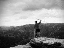 Man with forearm crutch. Hiker achieved mountain peak with broken leg in immobilize. Man with forearm crutch. Hiker finaly achieved mountain peak. Tourist with Stock Image