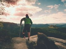 Man with forearm crutches. Hiker after hard walk achieved mountain peak. Tourist with broken leg. In immobilizer hold medicine  poles Royalty Free Stock Photography