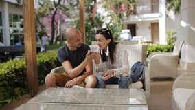 The tourist asks for help to the girl. The man is a foreigner talking to a girl through an interpreter on the phone. The man is a foreigner talking to a girl stock video footage
