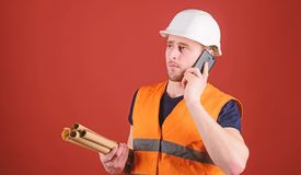 Man, foreman in helmet supervises construction on phone, red background. Architect concept. Engineer, architect, builder. On busy face speaks on smartphone royalty free stock images