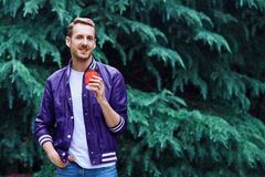 Man in the forest against green tree background with cup of coffee. Young smiling man wearing the purple blazer is drinking coffee from red cup in the forest royalty free stock photography