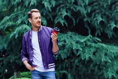 Man in the forest against green tree background with cup of coffee. Young smiling man wearing the purple blazer is drinking coffee from red cup in the forest royalty free stock photo