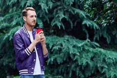 Man in the forest against green tree background with cup of coffee. Young smiling man wearing the purple blazer is drinking coffee from red cup in the forest royalty free stock image